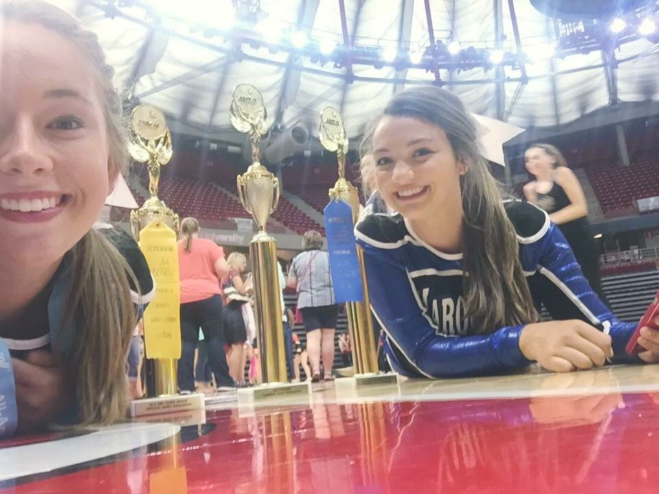 A couple Marquette dancers making their UDA trophies look gigantic